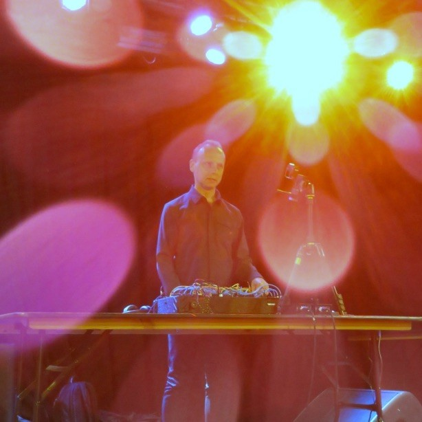 Photograph of a man in a very smart black shirt, standing on a stage in front of an electronic synthesiser, looking out into the audience. The stage lights are bright and glaring all around him