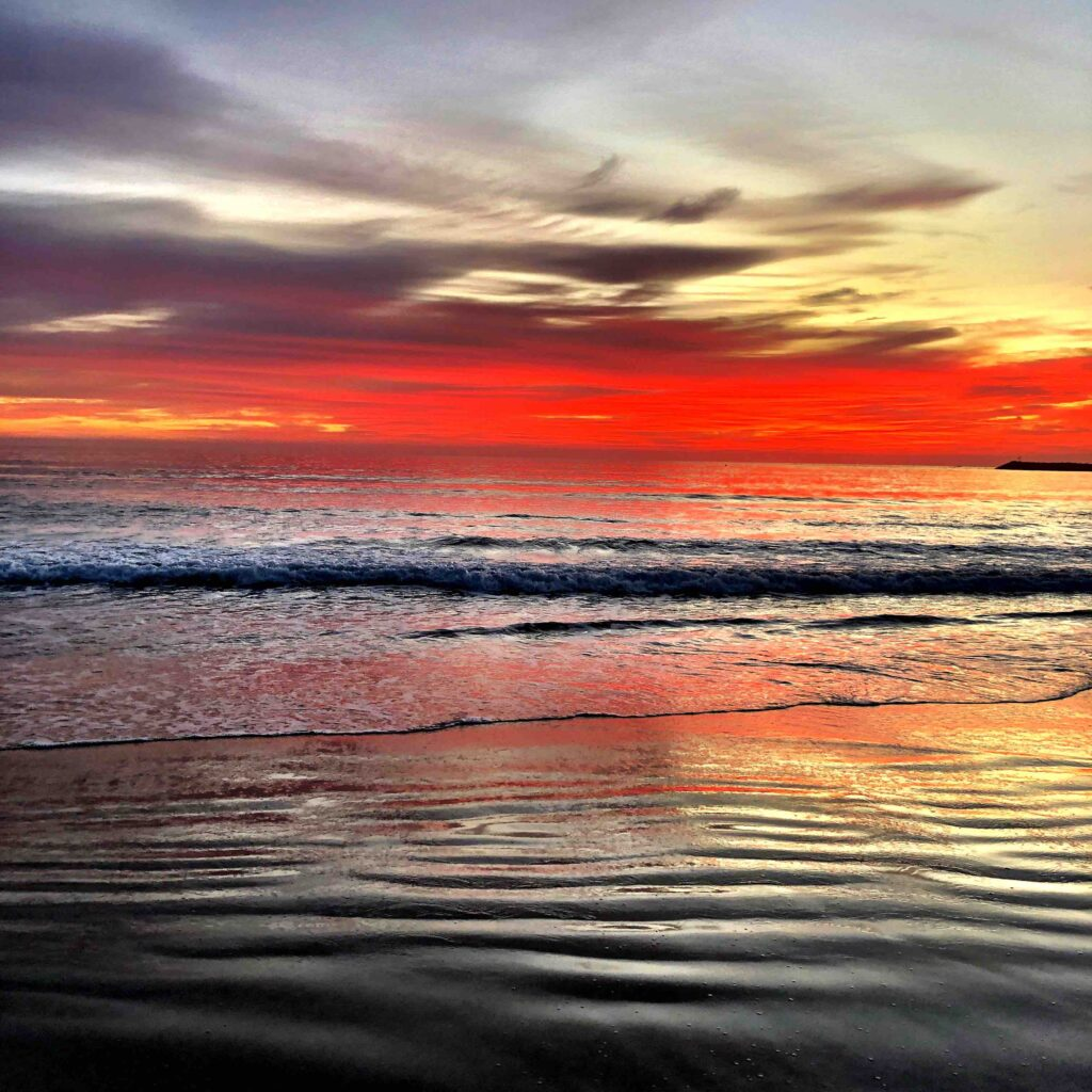 A picturesque image of the ocean with the skies alight with red colours and the water so calm and peaceful