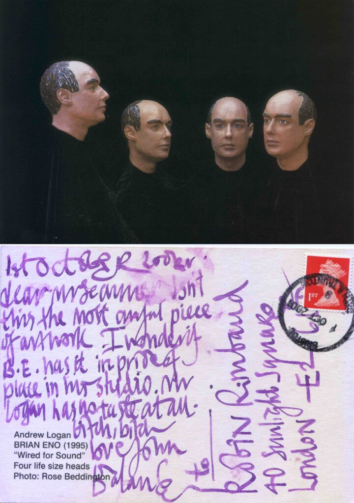 A postcard of a sculpture repeated four times with an image of the musician Brian Eno. Created by Andrew Logan 1995. Purple handwritten ink text on the rear of the card.