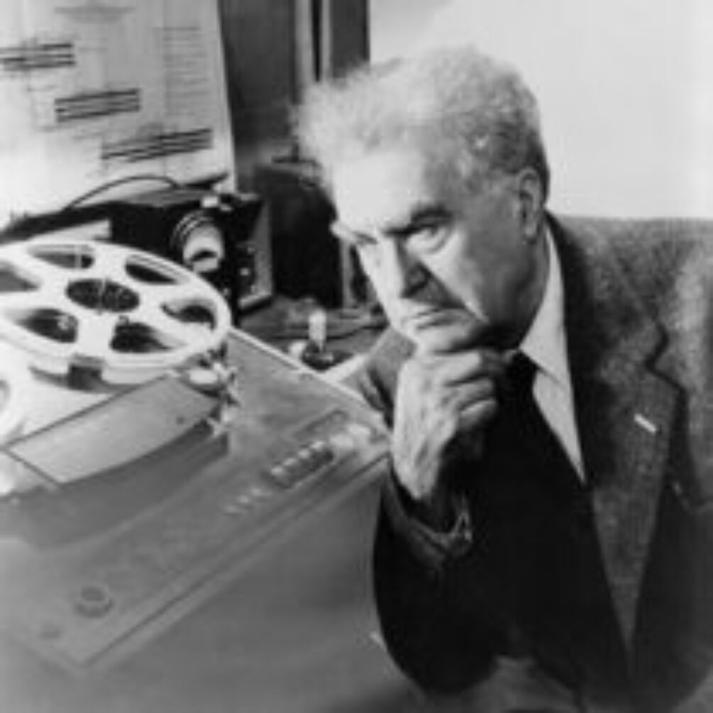 Black and white photography of elders man, with grey hair, in a smart black suit, leaning on his hand in though in a music studio. Behind him stands a old reel-to-reel tape player